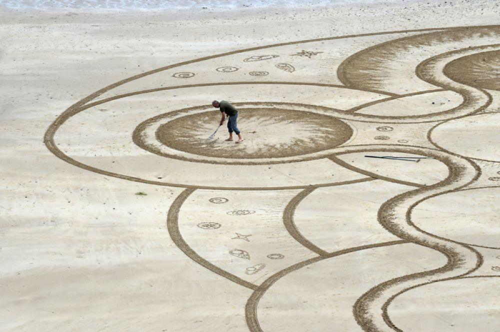7 июня. Художник Марк Тренор создаёт картины из песка на Северном пляже в гавани Тенби, Пембрукшир, Великобритания.
