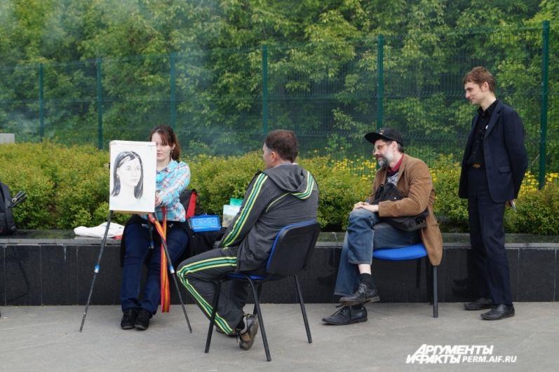 На набережной работают уличные художники.