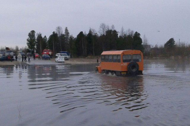 В Надыме на затопленном участке дороги работают грузовой трейлер и Урал.
