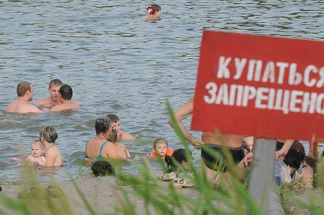 Люди купаются под запрещенными знаками.