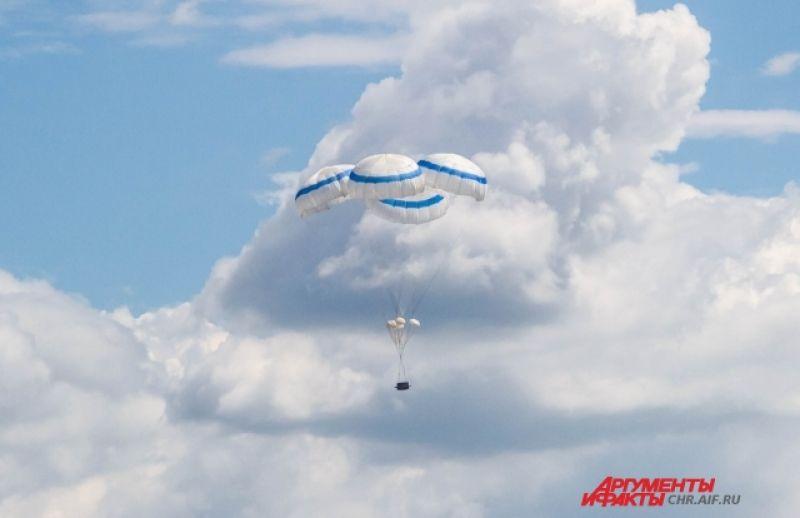 Из тяжелого Ил-76 выбрасывают груз, который плавно спускается на землю благодаря специальным парашютам-куполам