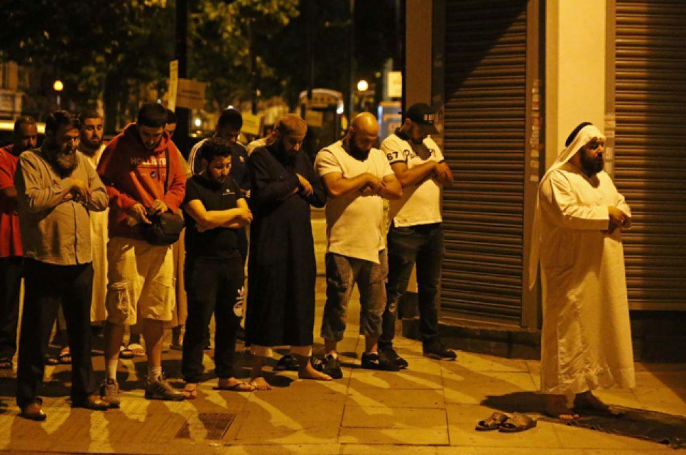 Мужчины молятся возле места происшествия в Лондоне.