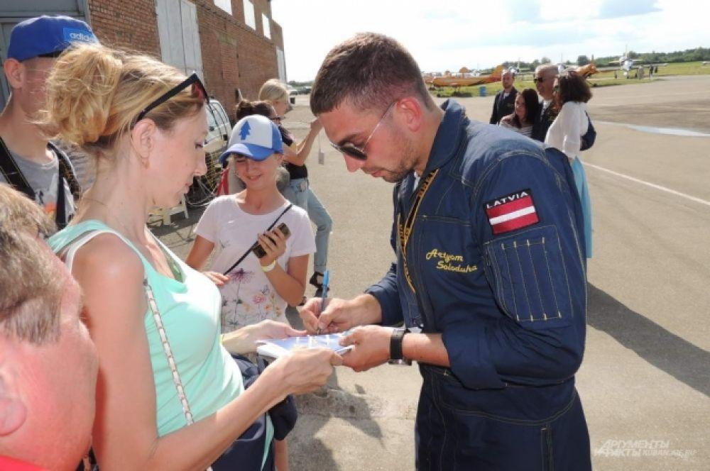 Пилот Артем Солодуха раздает автографы после выступления.