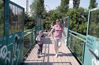 Сотни людей ходят по мосту, который держится на гнилых балках.