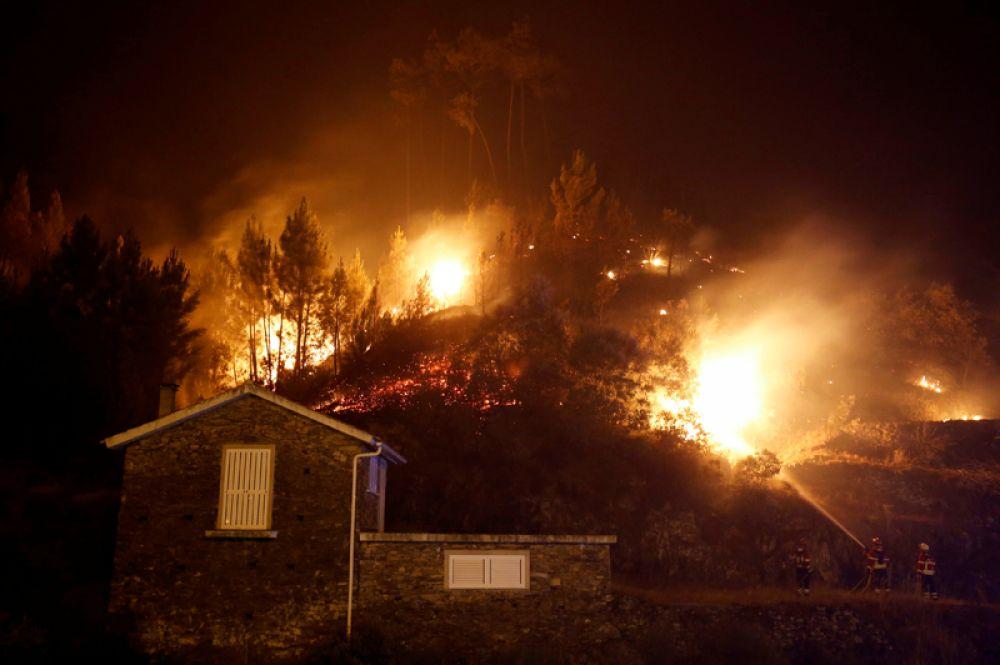 Пожарные пытаются спасти дом от лесного пожара в Карвальо.