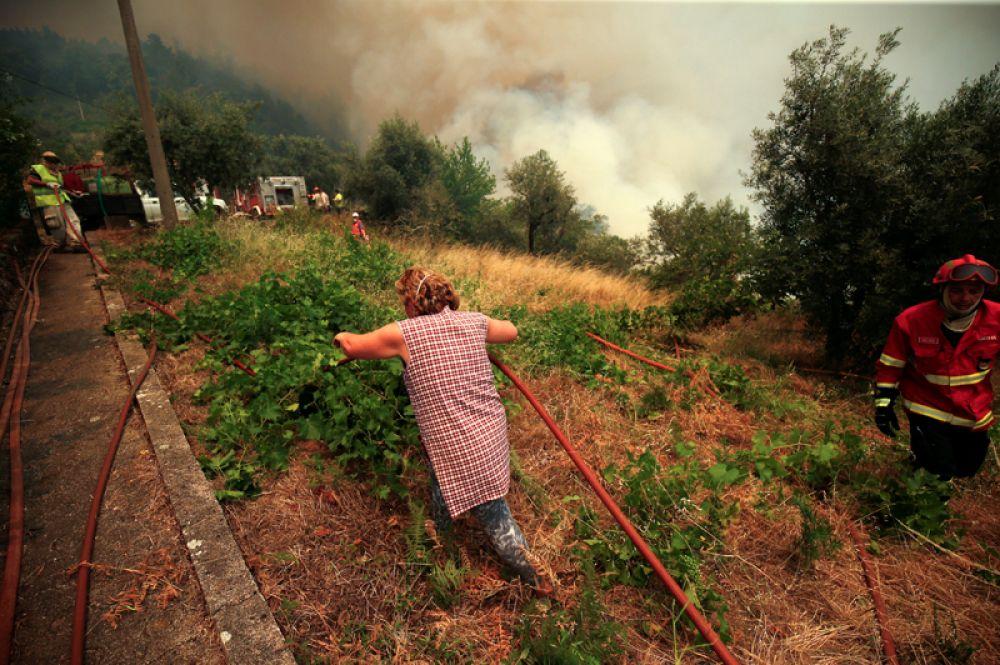Местные жители помогают спасателям бороться с огнём.