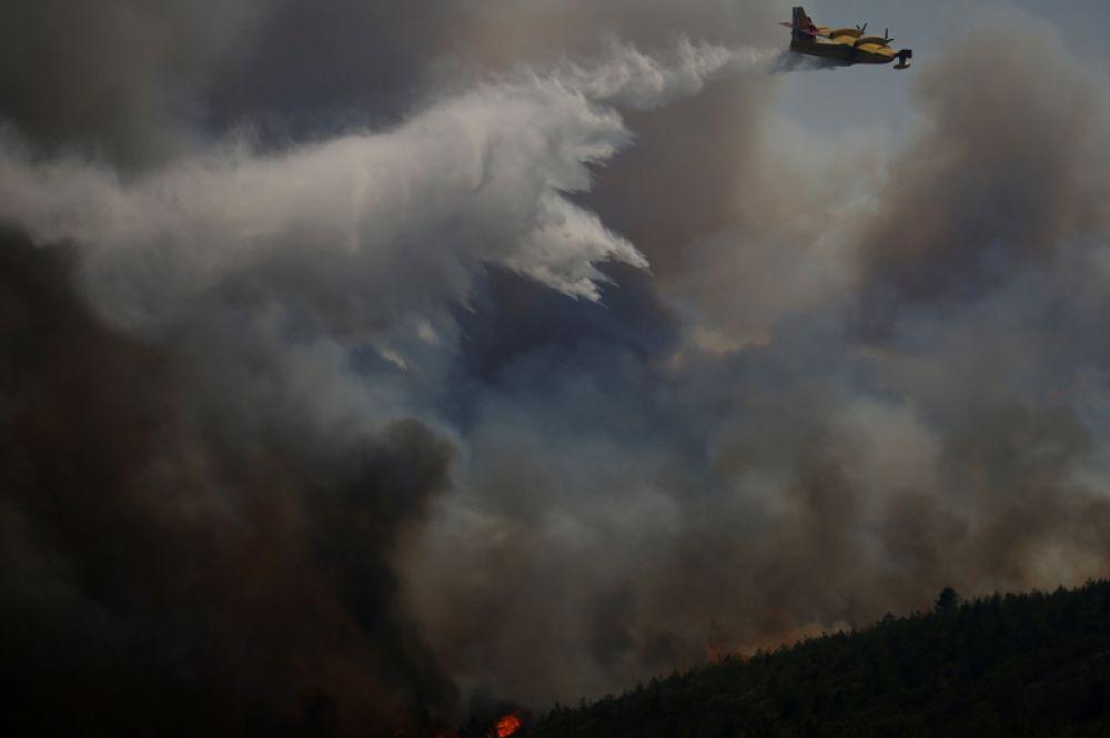 Пожарный самолёт тушит на лесной пожар в районе Кадафаш муниципалитета Гойш.