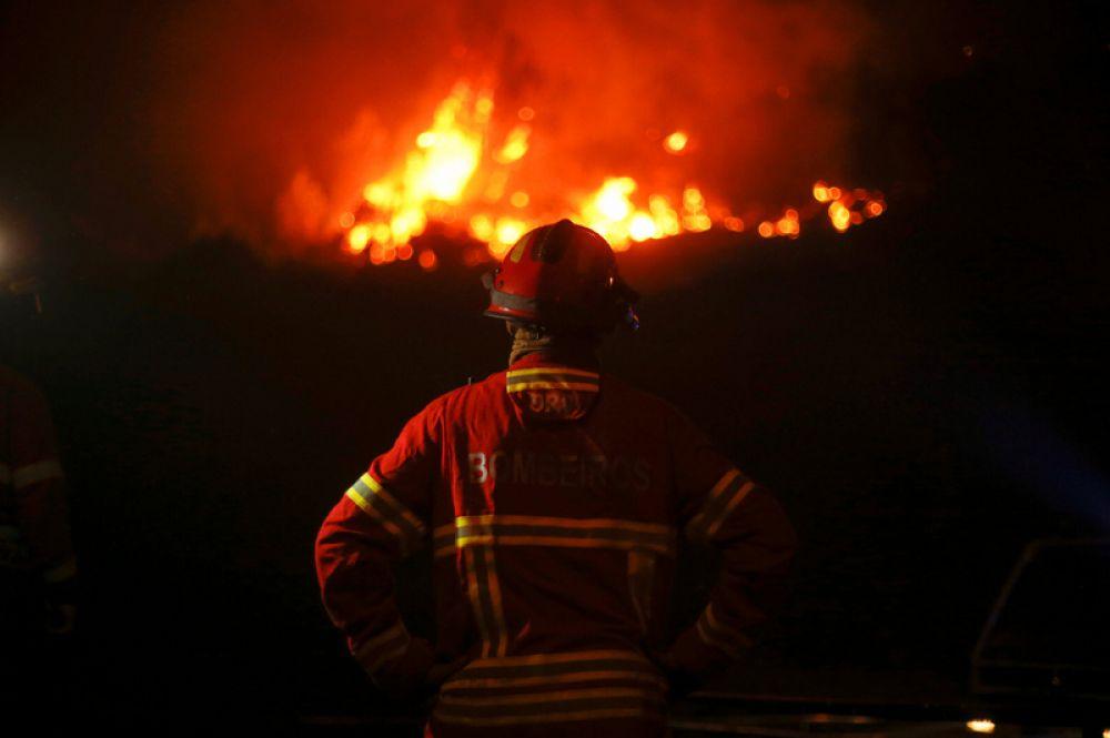 Пожарный наблюдает за приближающимся огнём в Карвальо.