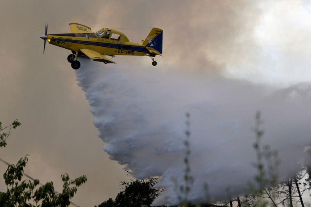 Испанский пожарный самолёт тушит на лесной пожар в округе Лорисейра.