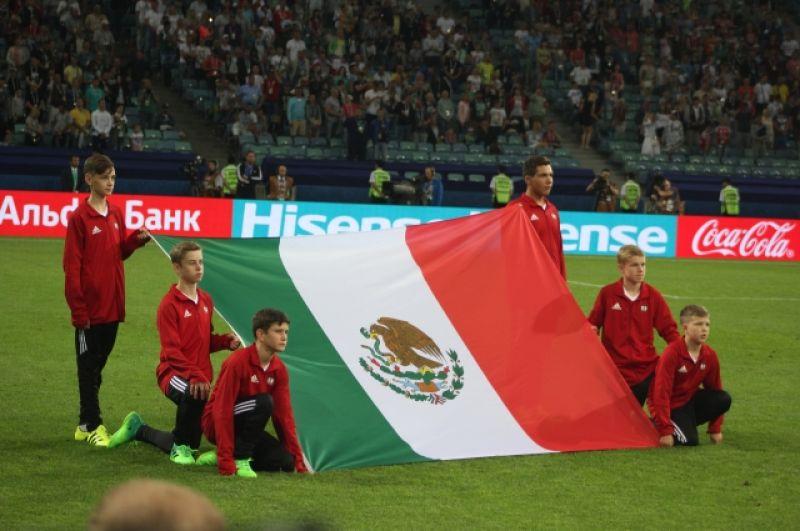 Юные футболисты торжественно выносят на поле флаг Мексики.