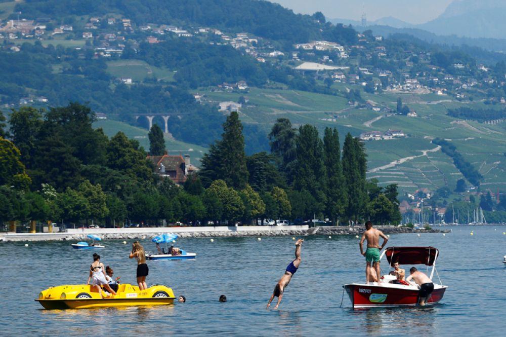 Люди наслаждаются солнечным днем на озере Леман. Лозанна, Швейцария, 21 июня 2017.
