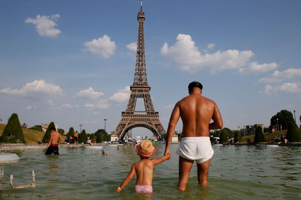 Люди купаются в фонтанах на площади Трокадеро возле Эйфелевой башни. Париж, Франция, 21 июня 2017 года.