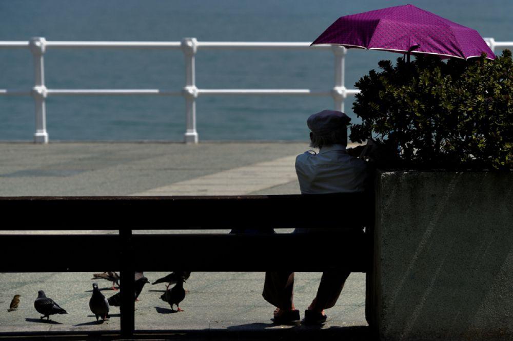 Мужчина прячется от солнца под зонтом. Хихон, Испания, 21 июня 2017 года.