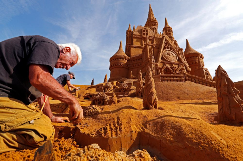 22 июня. Франко Дага из Италии работает над созданием скульптуры из песка во время фестиваля Disney Sand Magic в Остенде, Бельгия.