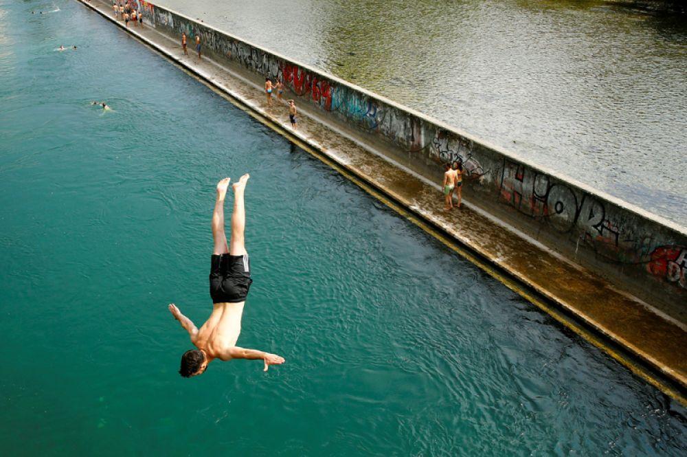 21 июня. Пока жители России всё ещё ждут наступления лета, в Европе установилась аномальная жара. Мужчина прыгает с моста в реку Лиммат. Цюрих, Щвейцария.