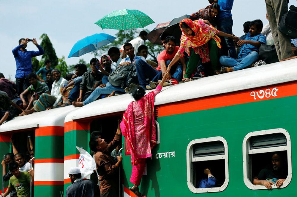 23 июня. Переполненный пассажирский поезд на железнодорожной станции в Дакке, Бангладеш. Пассажиры отправляются домой, чтобы отпраздновать праздник разговения Ид аль-Фитр (Ураза-Байрам).