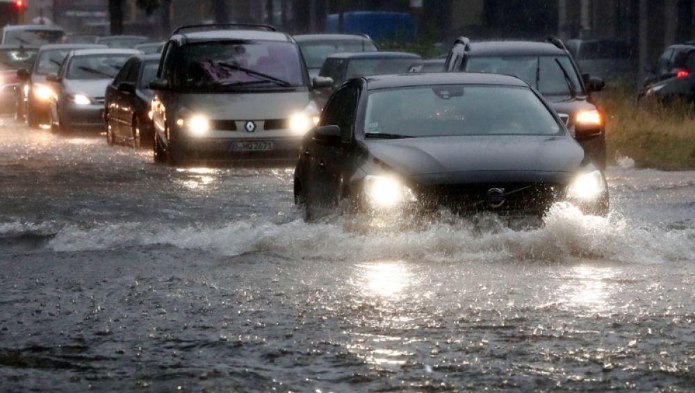 Машины на затопленной улице во время проливного дождя в Берлине.