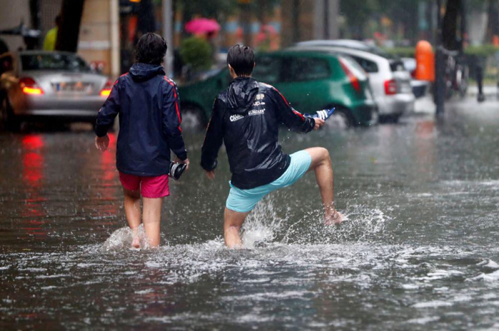 Люди на затопленной улице во время проливного дождя в Берлине.