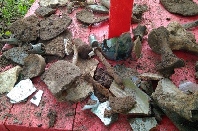 Находки археологов - наконечник стрелы, кости животных, керамика и стекло.