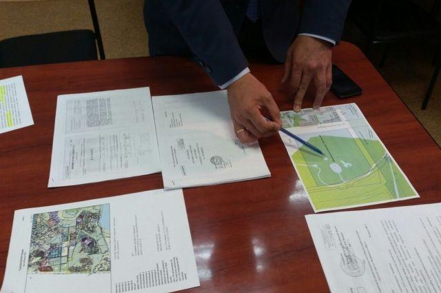 Сергей Самсонов показывает на карте, как новая дорога обогнёт братскую могилу и бывшие шахты.
