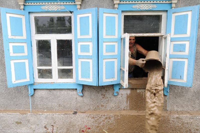 Мужчина вычерпывает воду из жилого дома, пострадавшего от наводнения в городе Крымск в Краснодарском крае.
