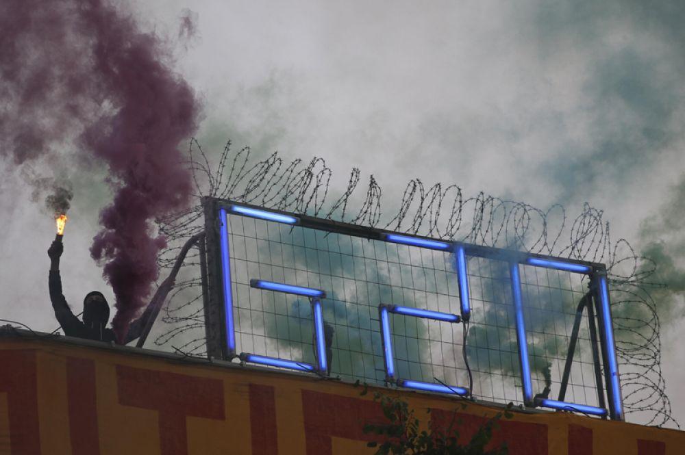 Мужчина с файером во время акции протеста перед саммитом G20.