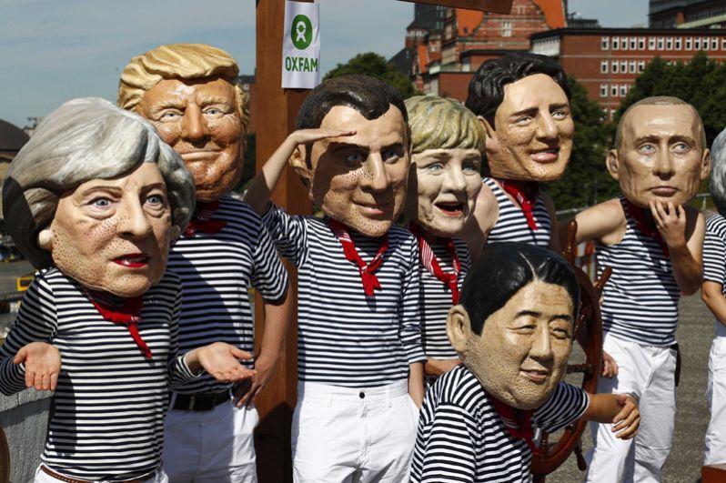 Активисты из OXFAM в масках мировых лидеров во время демонстрации в гавани Гамбурга.