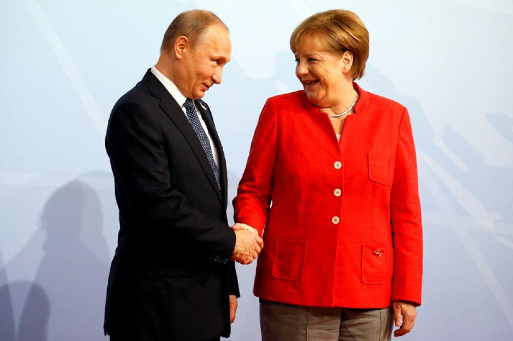 Канцлер Германии Ангела Меркель приветствует президента России Владимира Путина на саммите G20 в Гамбурге.