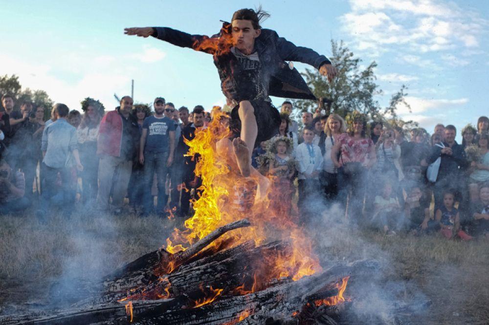 6 июля. Мужчина прыгает через костер на празднике Ивана Купала в Киеве.