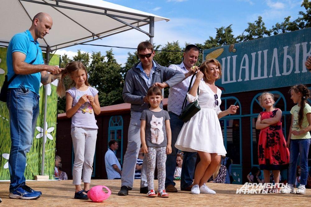 На празднике выбирали лучшего папу: в одном из конкурсов отцам нужно было сделать дочери красивую причёску.