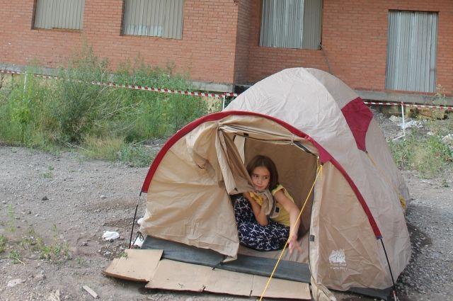 Люди поставили палатки рядом с недостроенным домом.