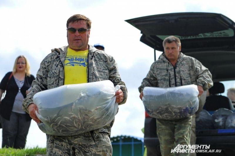 Мешки перевозят к лодкам.