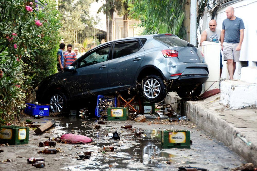 Повреждённый автомобиль на улицах города Гюмбет в Турции.