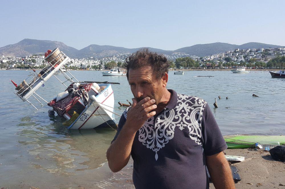 Местный житель после землетрясения в курортном городе Гюмбет в Турции.
