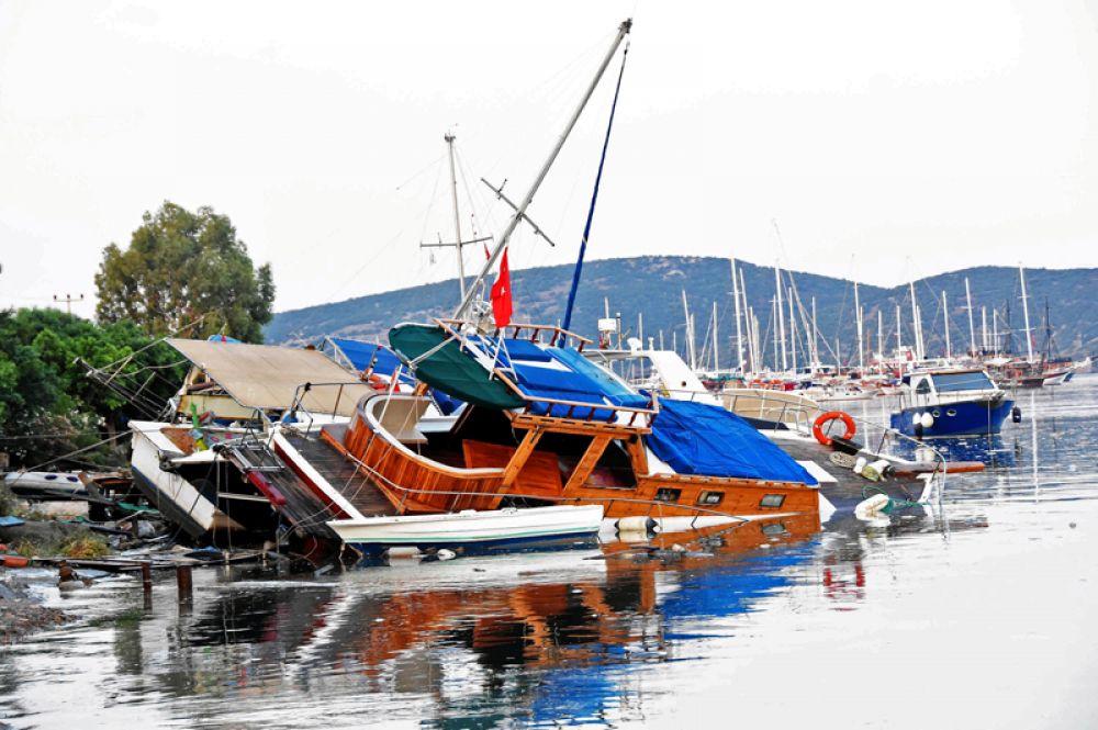 Затопленные лодки после землетрясения и цунами в курортном городе Гюмбет в провинции Мугла в Турции.