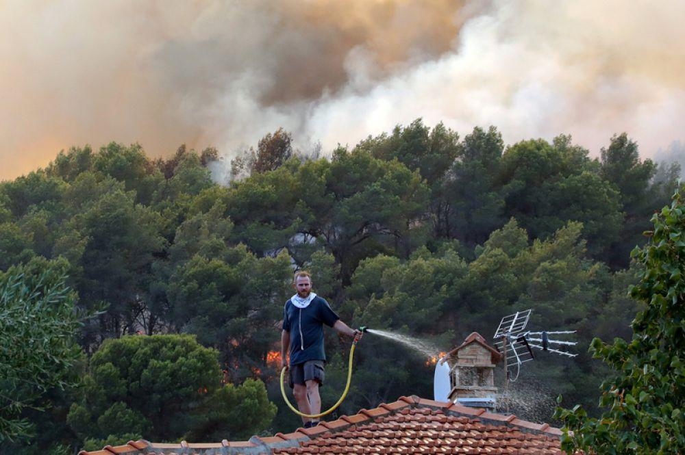 Местный житель на крыше своего дома пытается самостоятельно бороться с огнём, Франция.