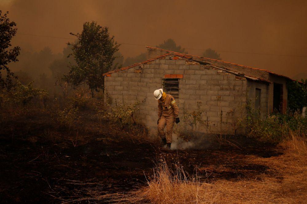 Пожарный борется с огнем в деревне Карвоэйру, Португалия.