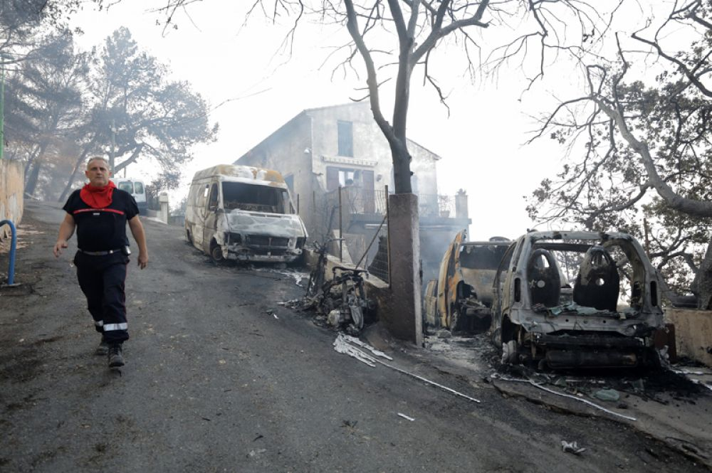 Пожарный идёт мимо сгоревших автомобилей в Карро, Франция.