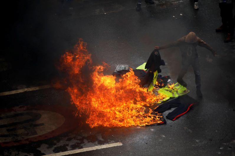 Демонстрант сжигает полицейскую форму на улицах Каракаса.