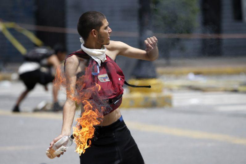 Демонстрант бросает коктейль Молотова во время протестов в Каракасе.