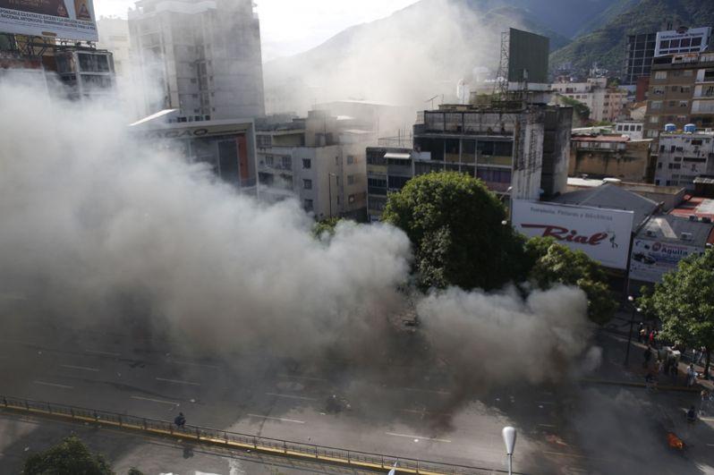 Горящие покрышки на дороге и подожженный полицейский участок в столице Венесуэлы.