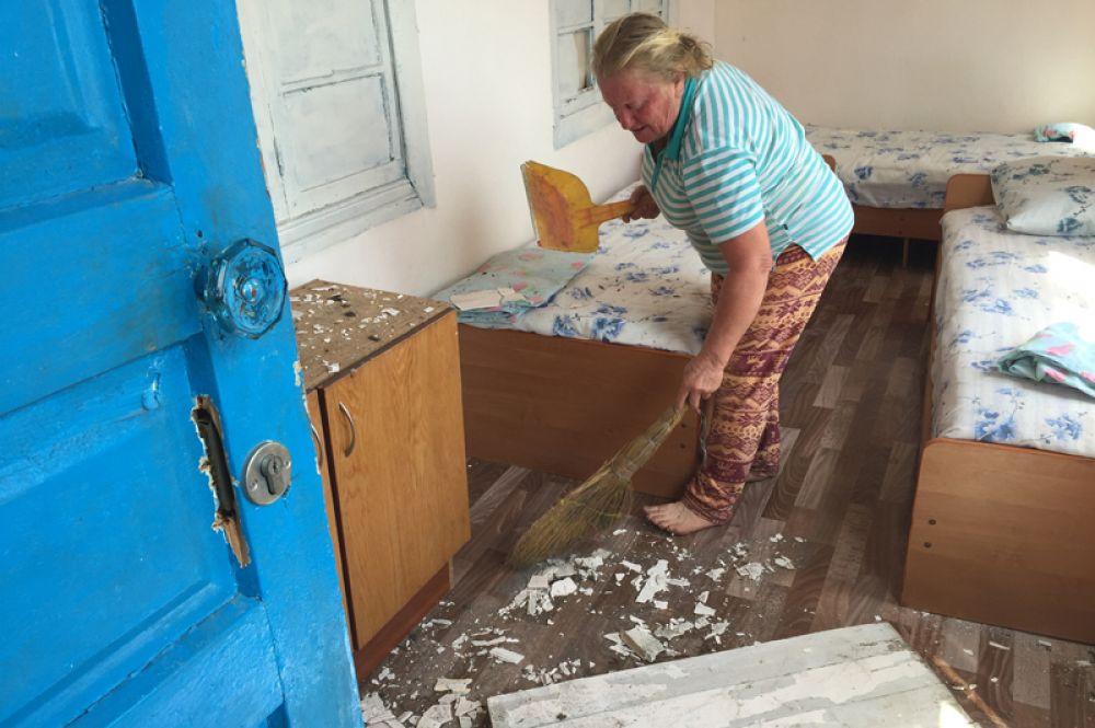 Женщина делает уборку в поврежденном доме в селе Приморское Гудаутского района.