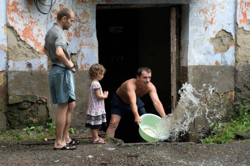 Мужчина вычерпывает воду из подъезда на затопленной улице Уссурийска.