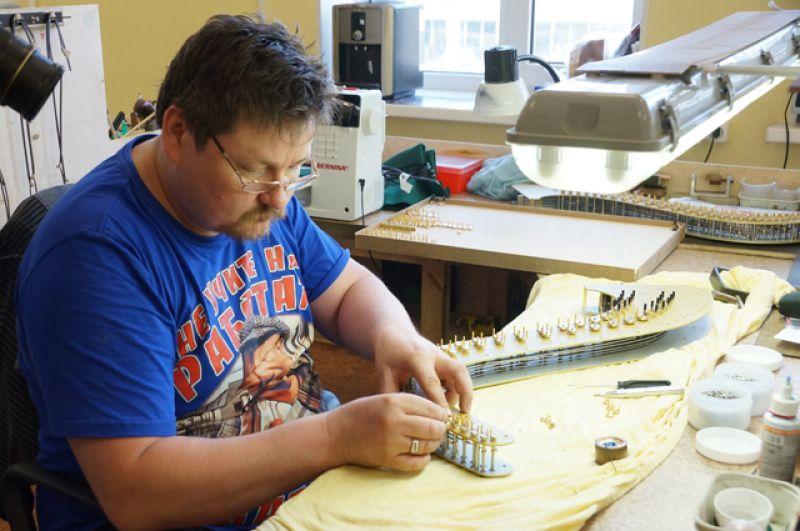 Слесарь-сборщик Владимир Тимофеев собирает механизм, где крепятся струны.
