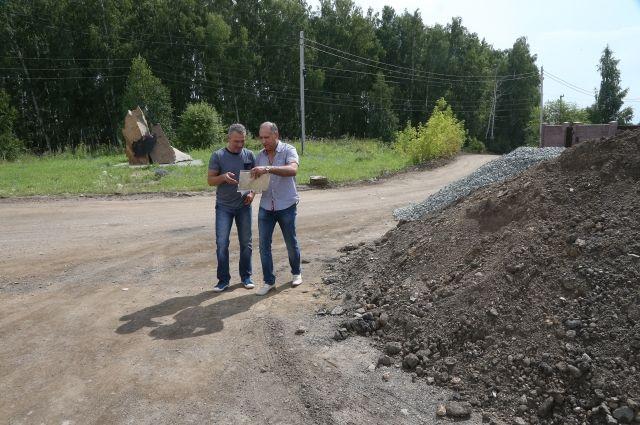 Жители посёлка идут по дороге, которой больше 20 лет. Теперь она изменит своё направление, а вот поклониться памятнику будет возможно, если зайти к нему сзади.