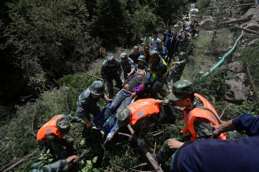 Китайские спасатели несут пострадавшего после землетрясения в округе Цзючжайгоу.