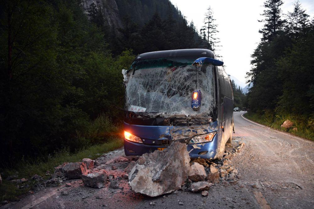 Автобус, пострадавший от упавших камней на шоссе S301 в уезде Цзючжайгоу провинции Сычуань на юго-западе Китая.