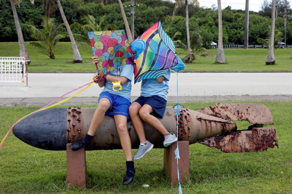11 августа. Школьники сидят на остатках торпеды времён Второй мировой войны в Мемориальном парке на острове Гуам, тихоокеанской территории США.
