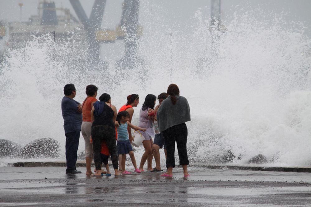 Семья наблюдает за высокими волнами во время шторма.
