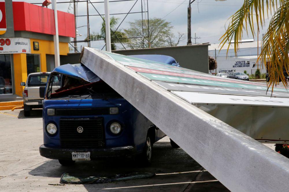 Поврежденный упавшим щитом автомобиль на бензозаправке Pemex после урагана.